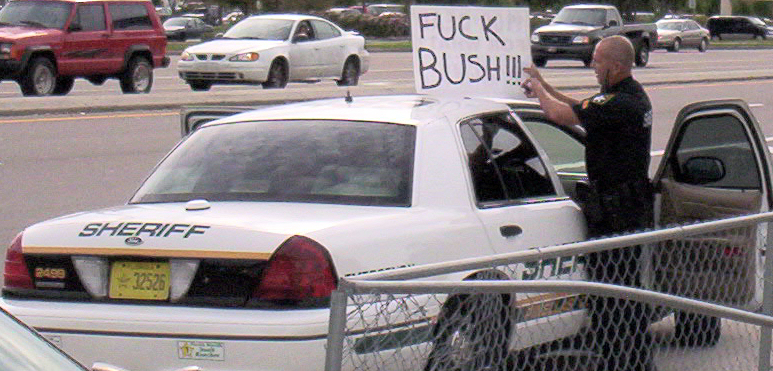 cop.with.fuck.bush.sign.773wide.jpg